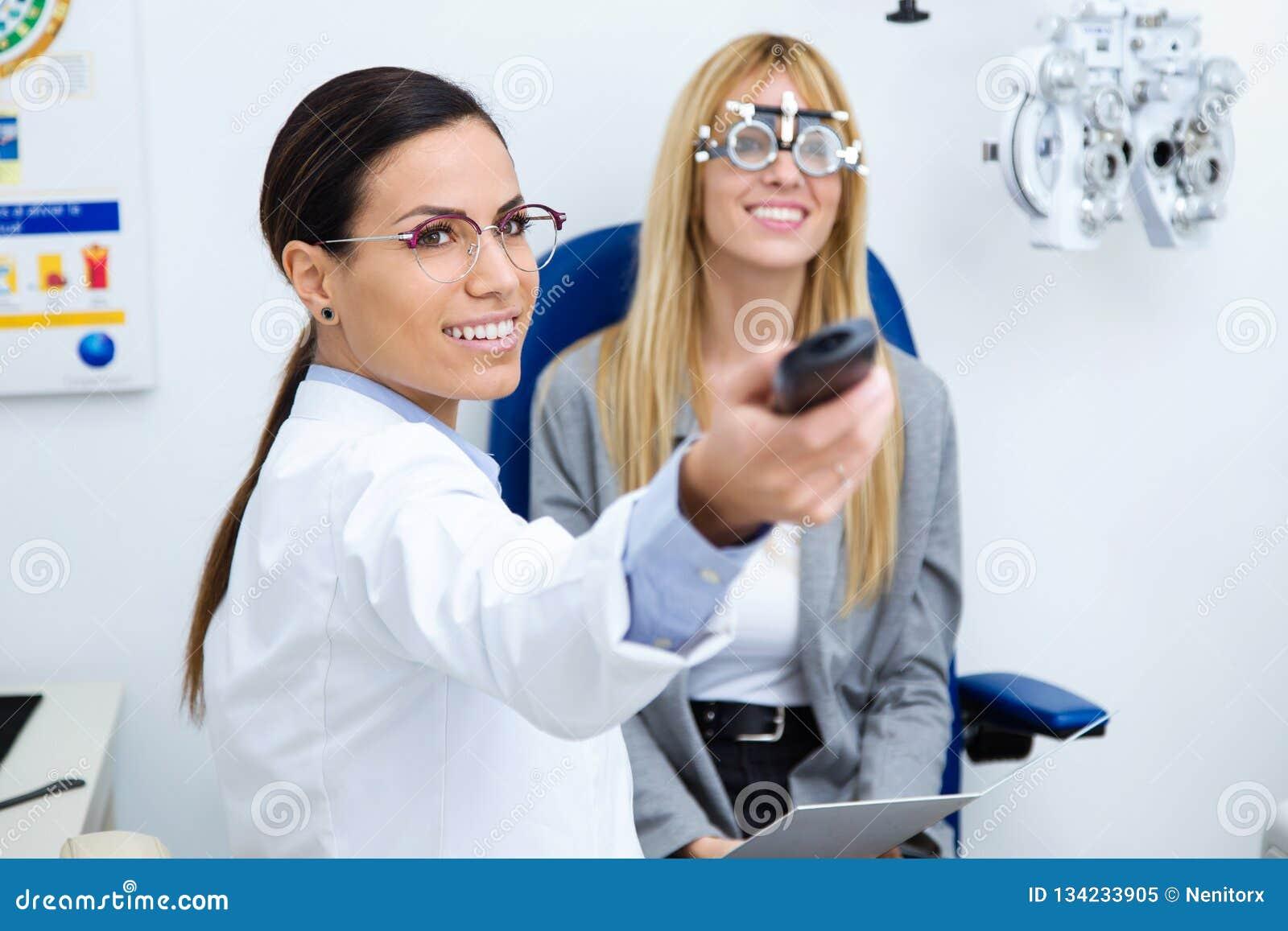 Optometrist женщины с пробной рамкой проверяя зрение пациента на клинике глаза Селективный фокус на докторе
