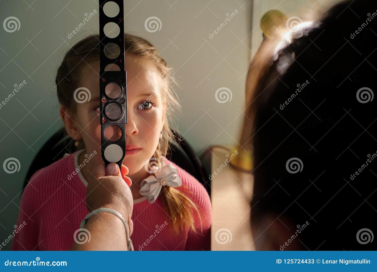 Optometry pojęcie - lekarz medycyny egzamininuje małej dziewczynki z magnifier