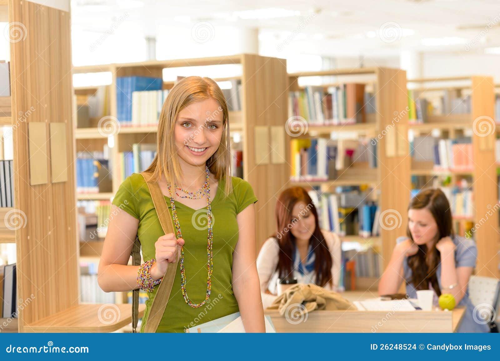 Opuszczać bibliotecznej szkoły średniej uśmiechnięta studencka dziewczyna