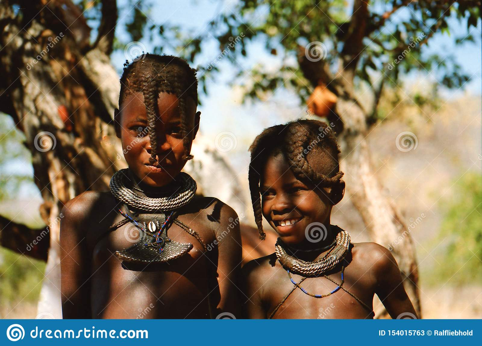 OPUWO, NAMIBIE DU NORD - 8 MAI 2013 : Fermez-vous de deux garçons de Himba avec le fond d arbres