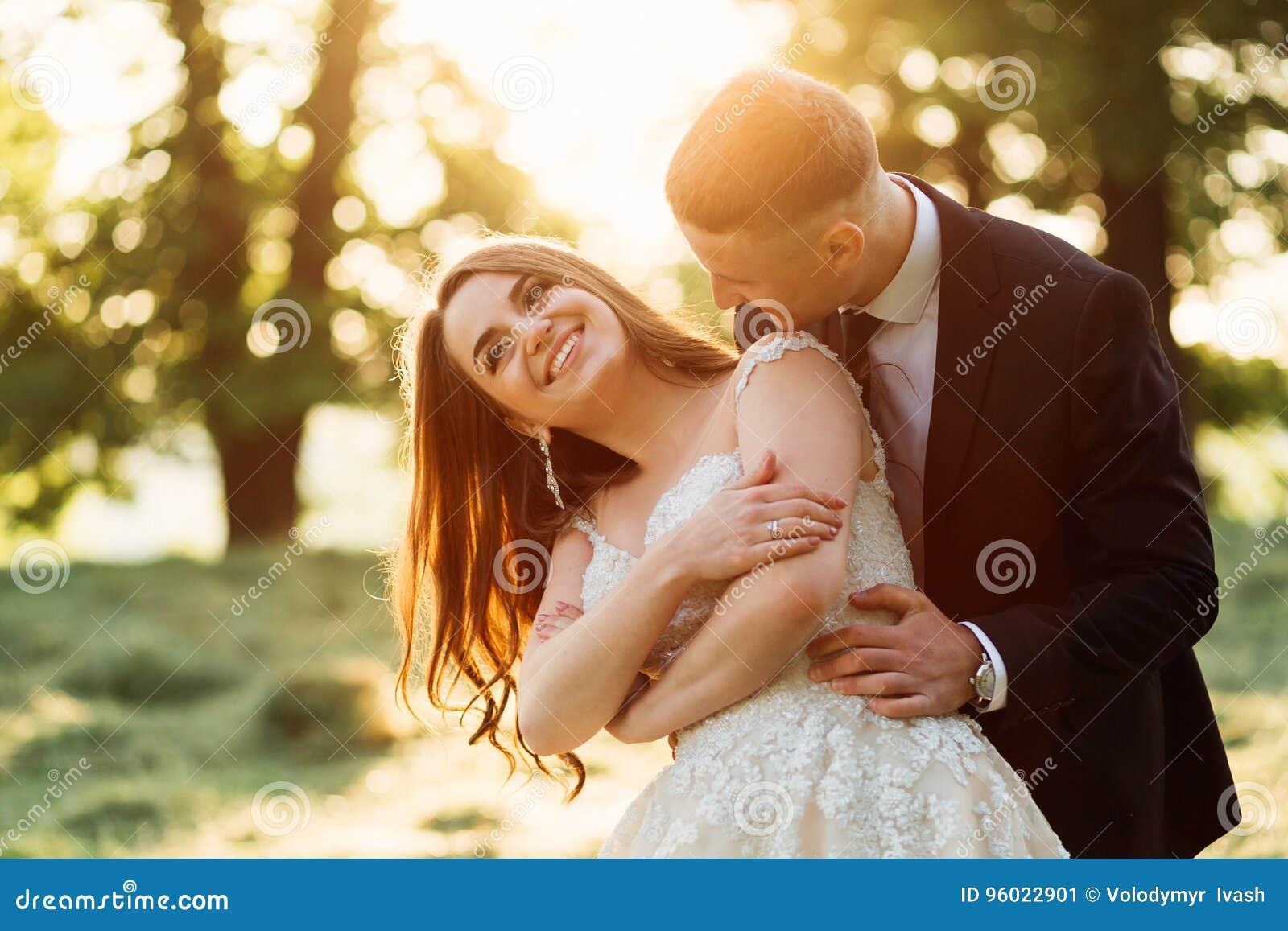 Opwindende bruidlach die zich in groom& x27 bevinden; s omhelzingen