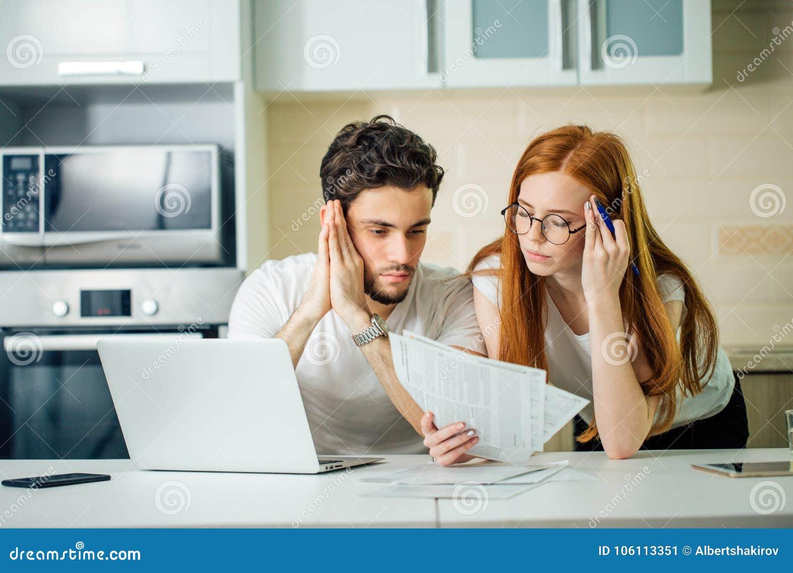 Orçamento de controlo da família, revendo suas contas bancárias usando o portátil na cozinha