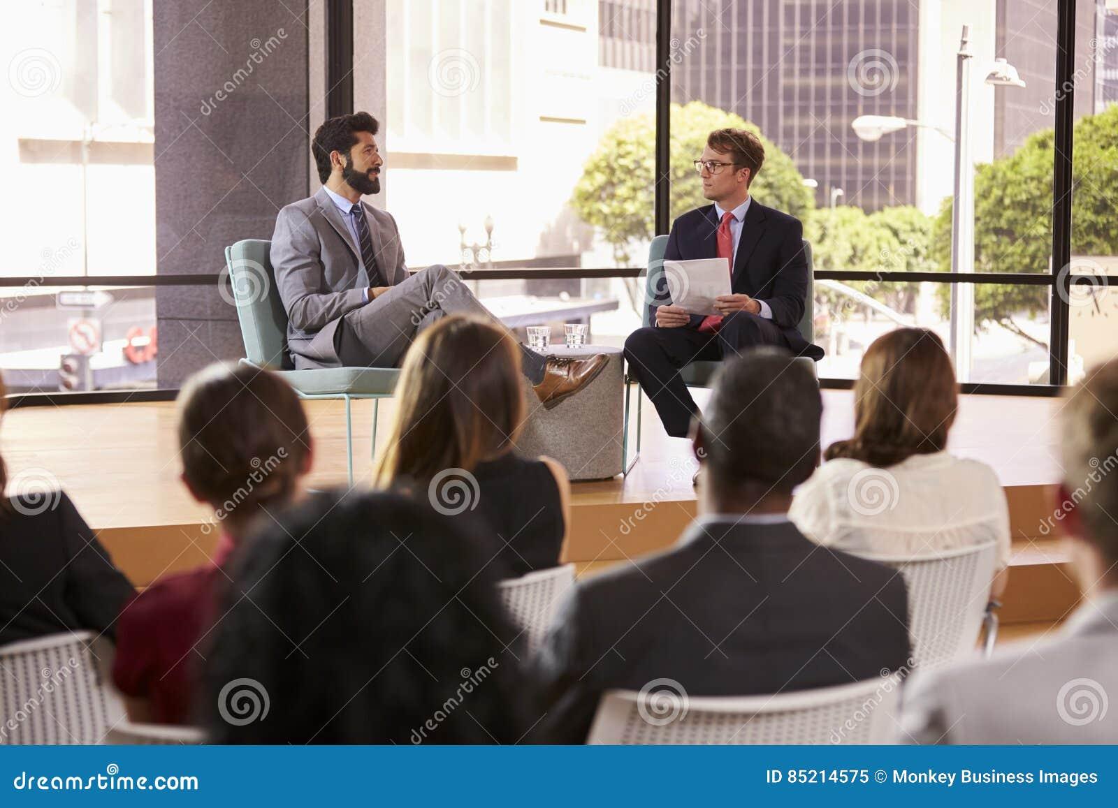 Orador e entrevistador na frente da audiência em um seminário