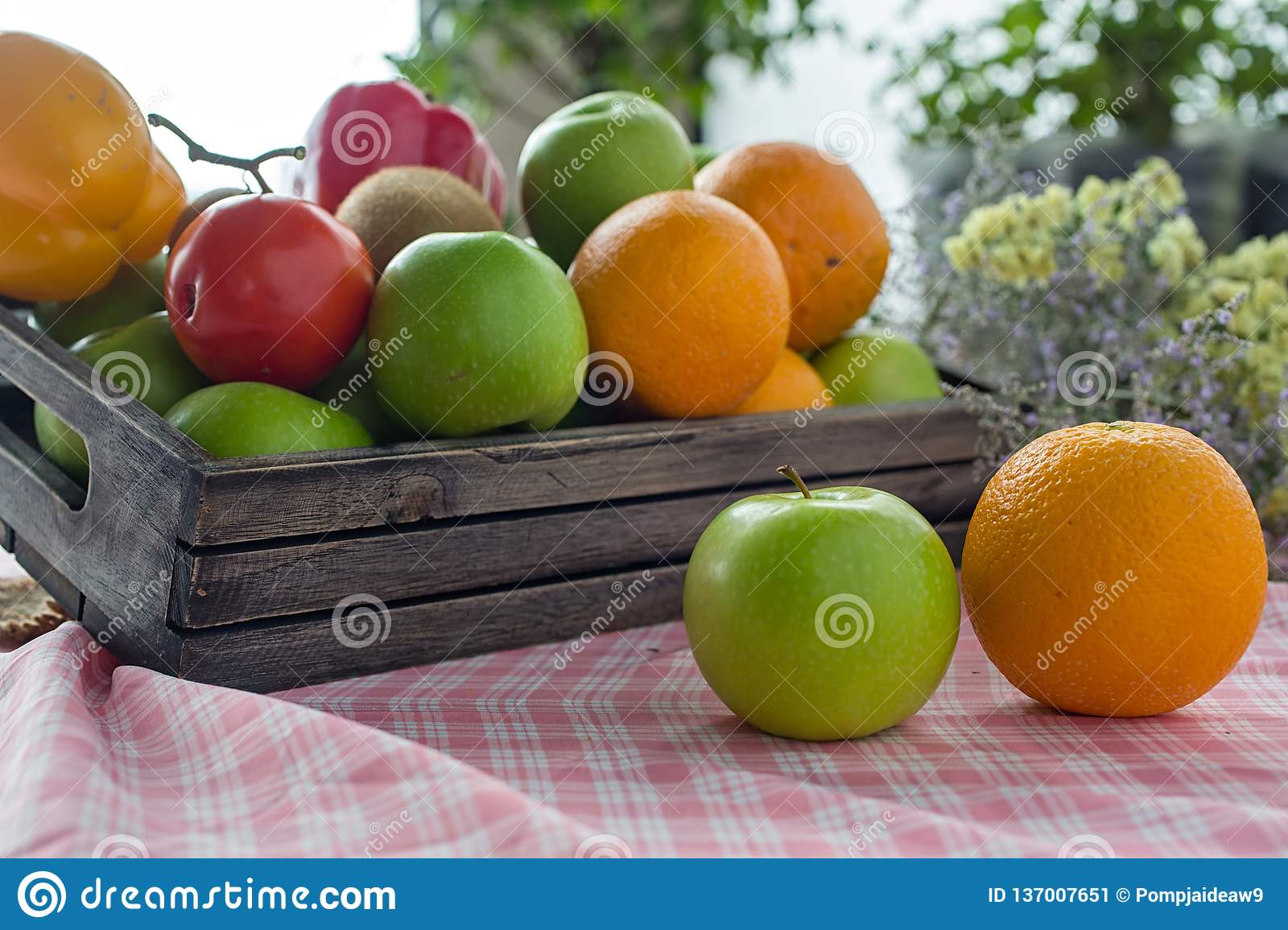 Orange and apple in a wooden crate. Fresh fruit on a wooden table with a cloth. Eating fruit helps to lose weight. fruits and