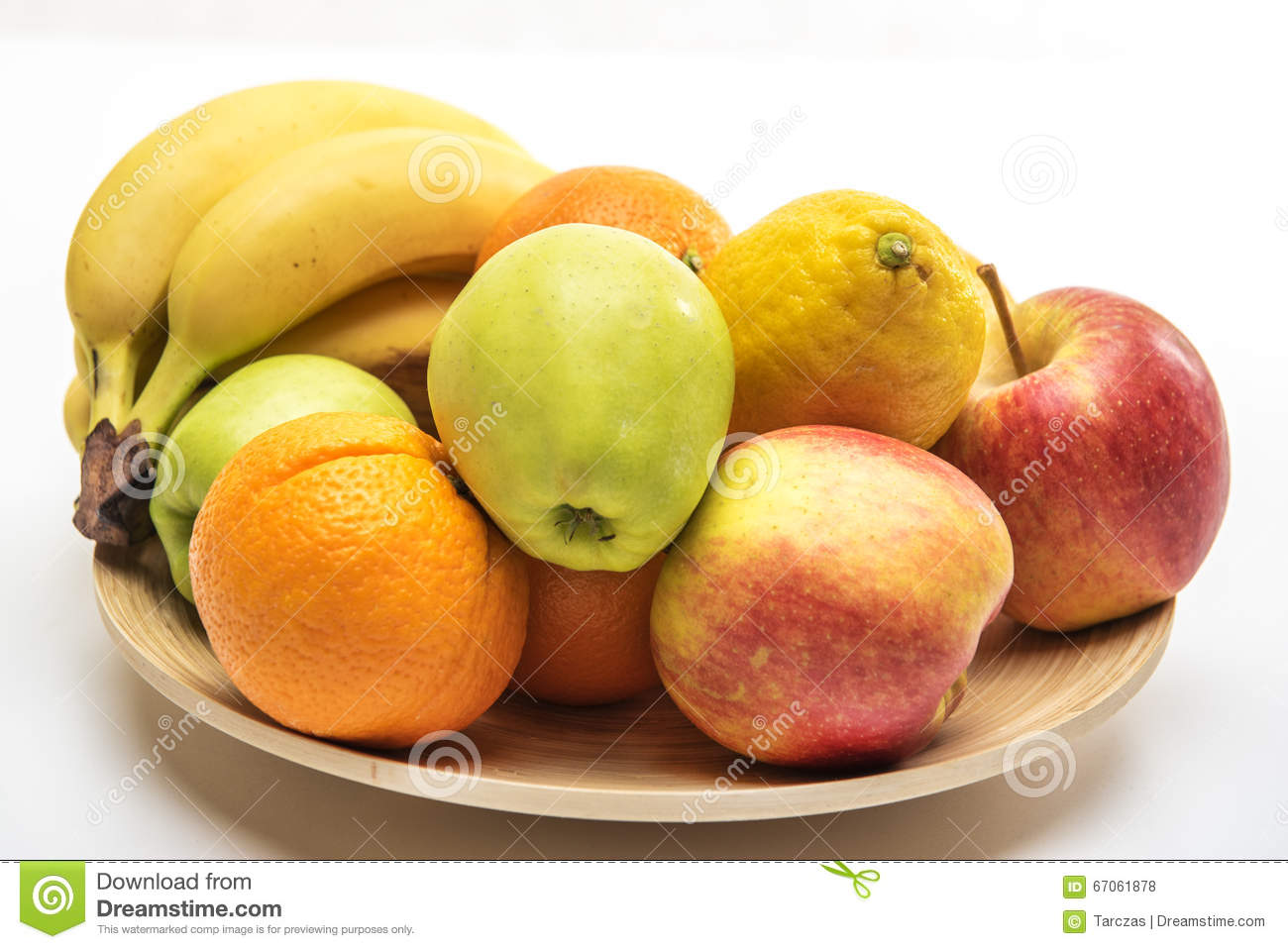Orange, apples and banana on the wooden plate