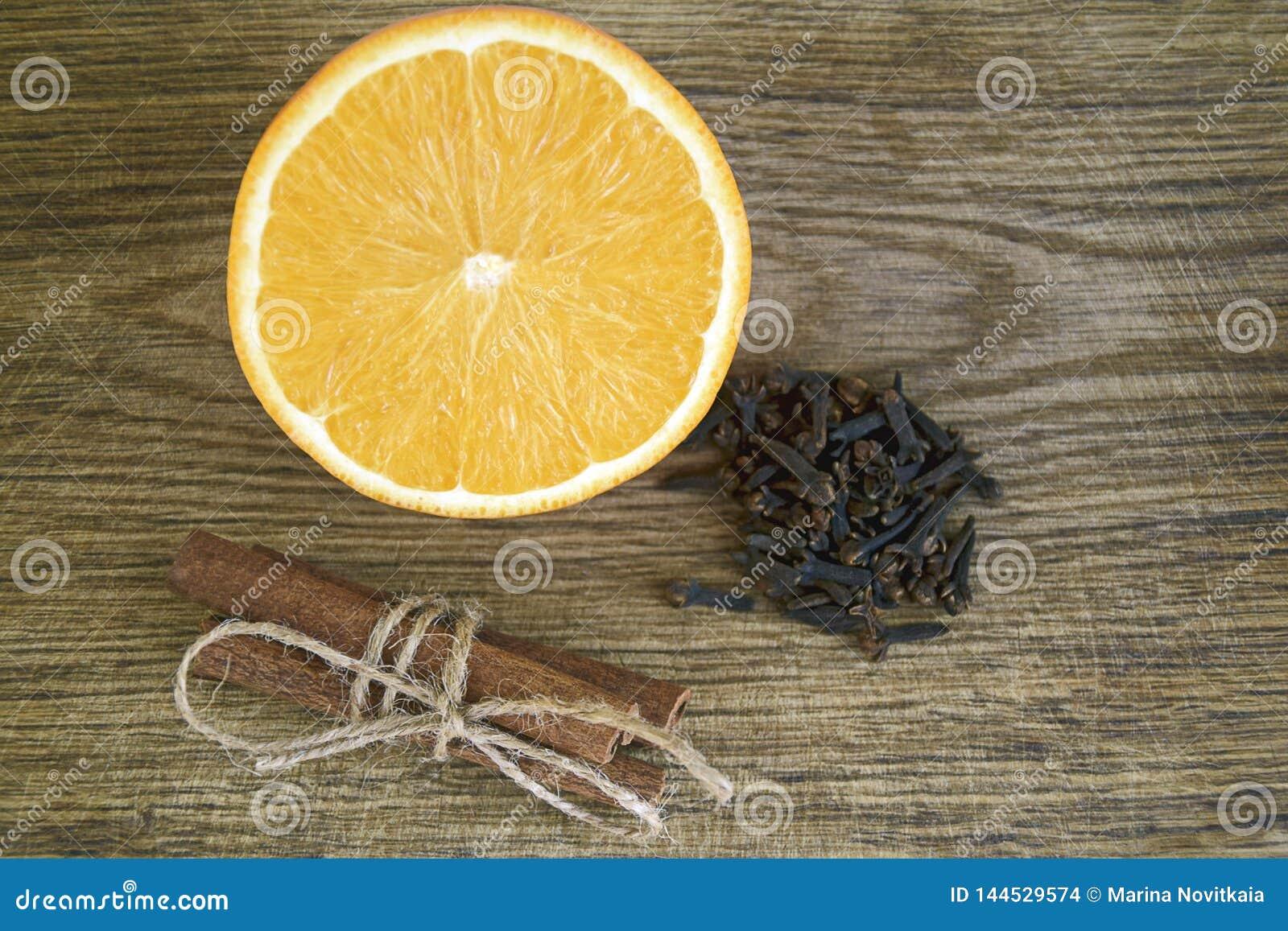 Orange, bâtons de cannelle, clous de girofle sur le fond en bois