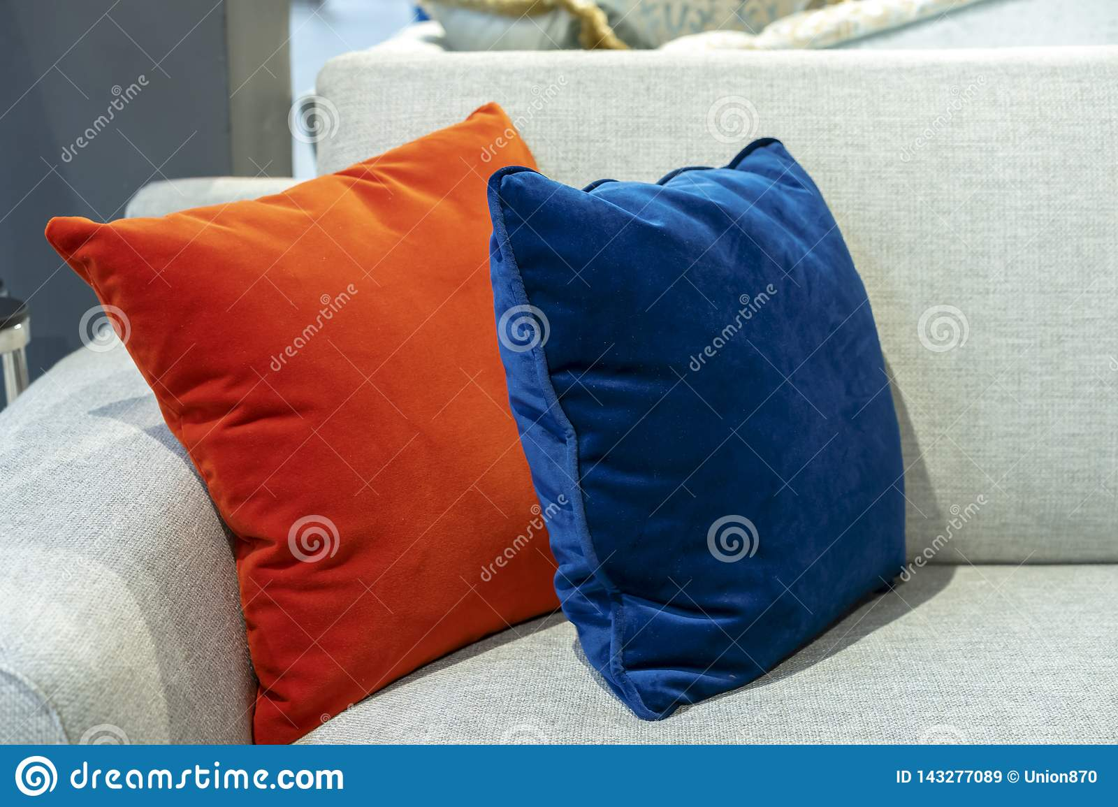 Orange And Blue Decorative Pillows On A Beige Sofa Stock