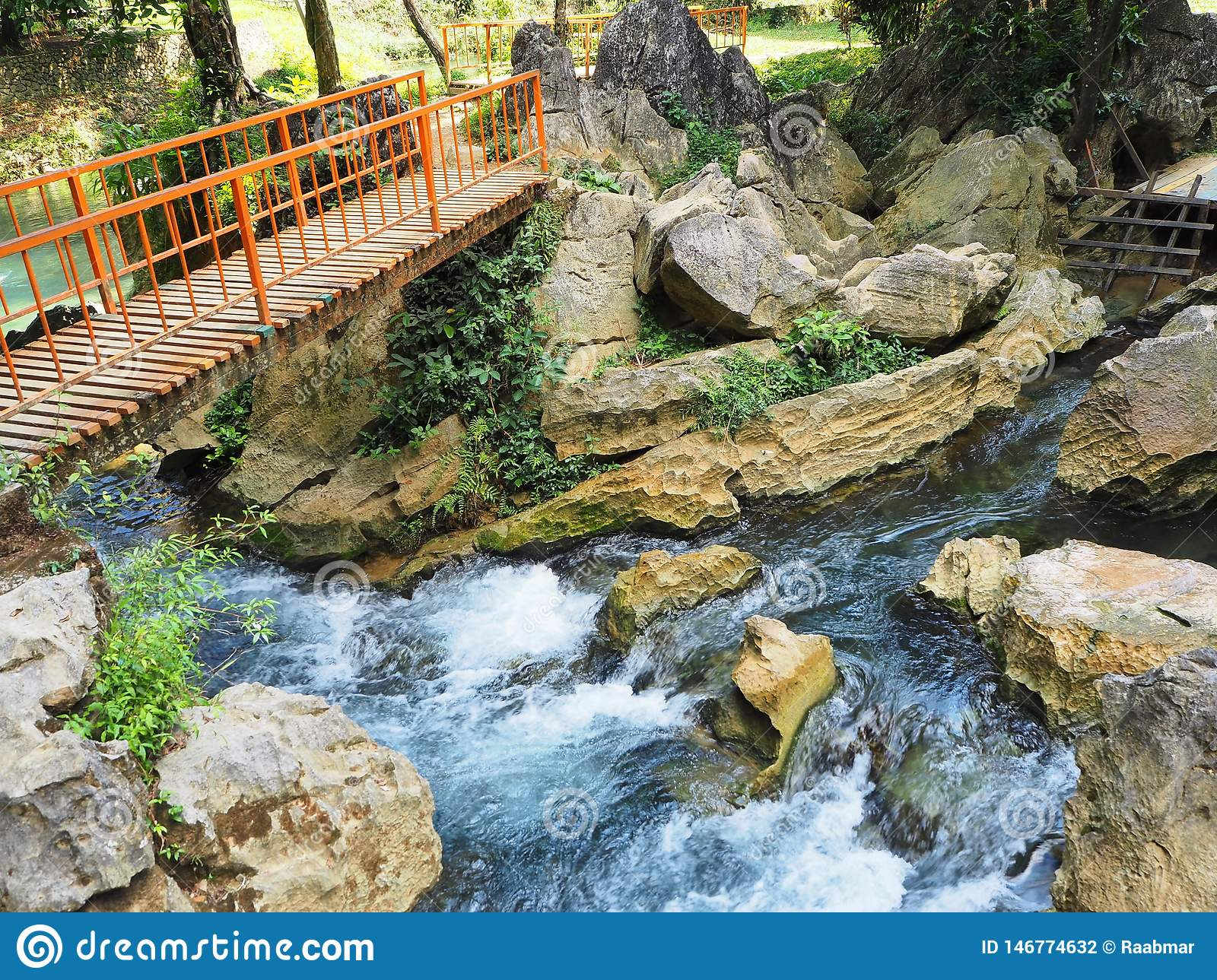 Orange bridge to cross a beautiful and colorful little river in Vang Vieng, Laos
