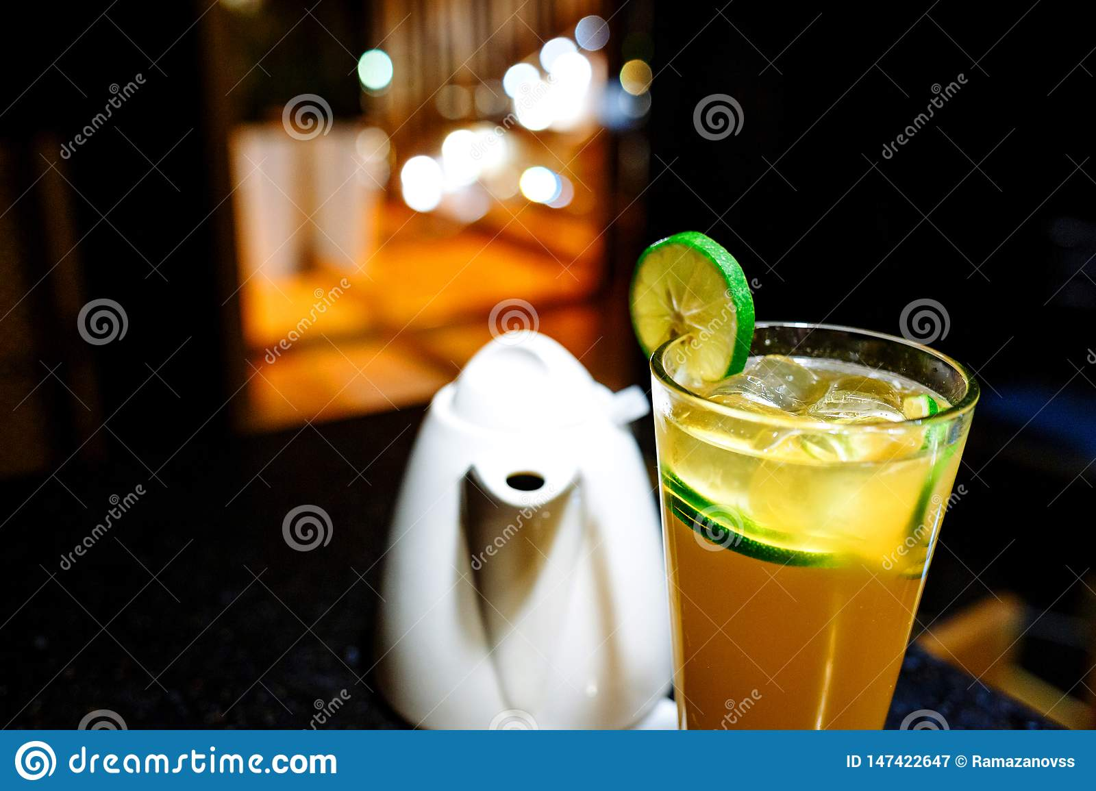 Orange cocktail with lime and teapot on dark background
