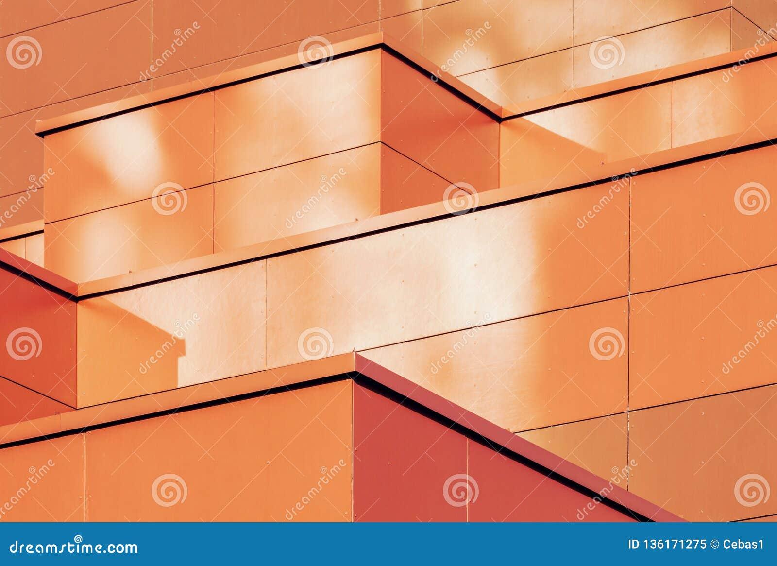 Orange colored geometric background of metal building facade