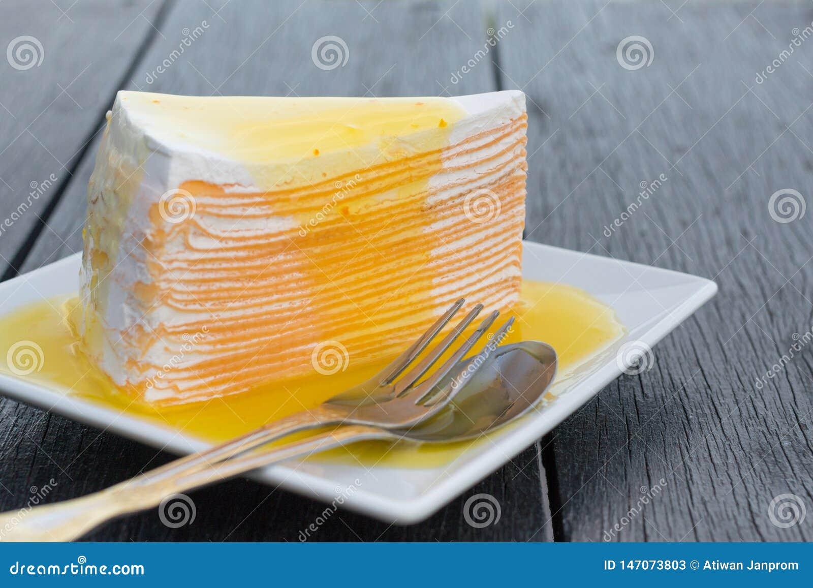 Orange crepe cake in white dish on black wooden table