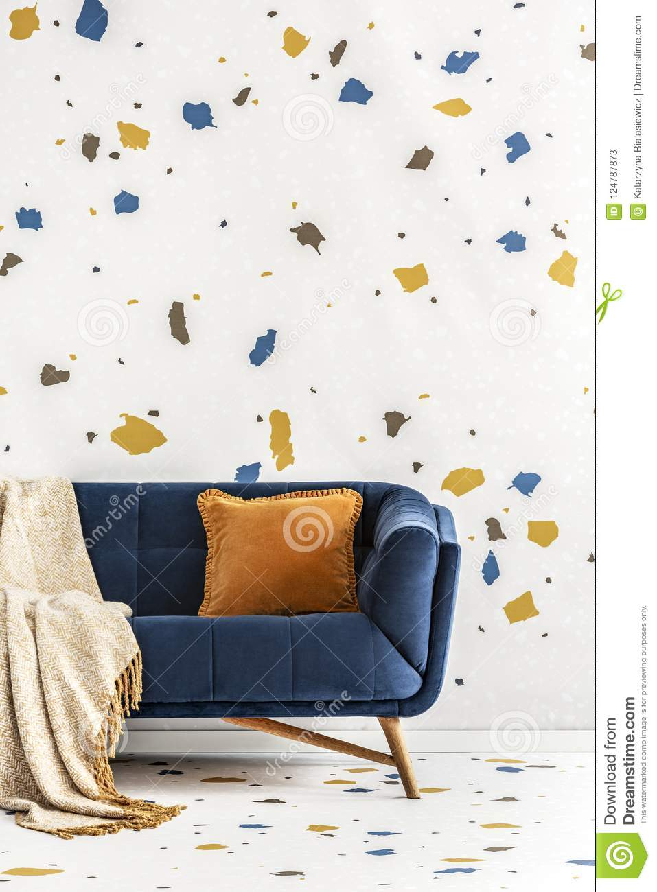 Orange cushion and blanket on blue sofa in colorful living room interior with wallpaper. Real photo