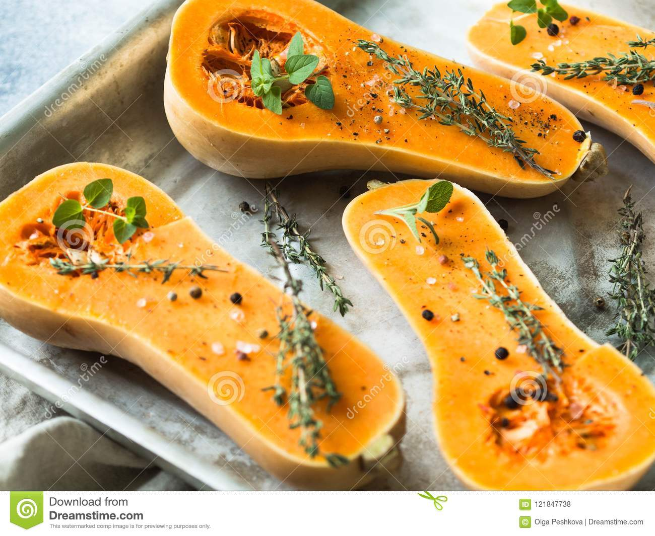Orange fresh pumpkin cooking with spice and herbs. cut pumpkin slices on a baking sheet. Fresh orange muscat gourd cut in half, re