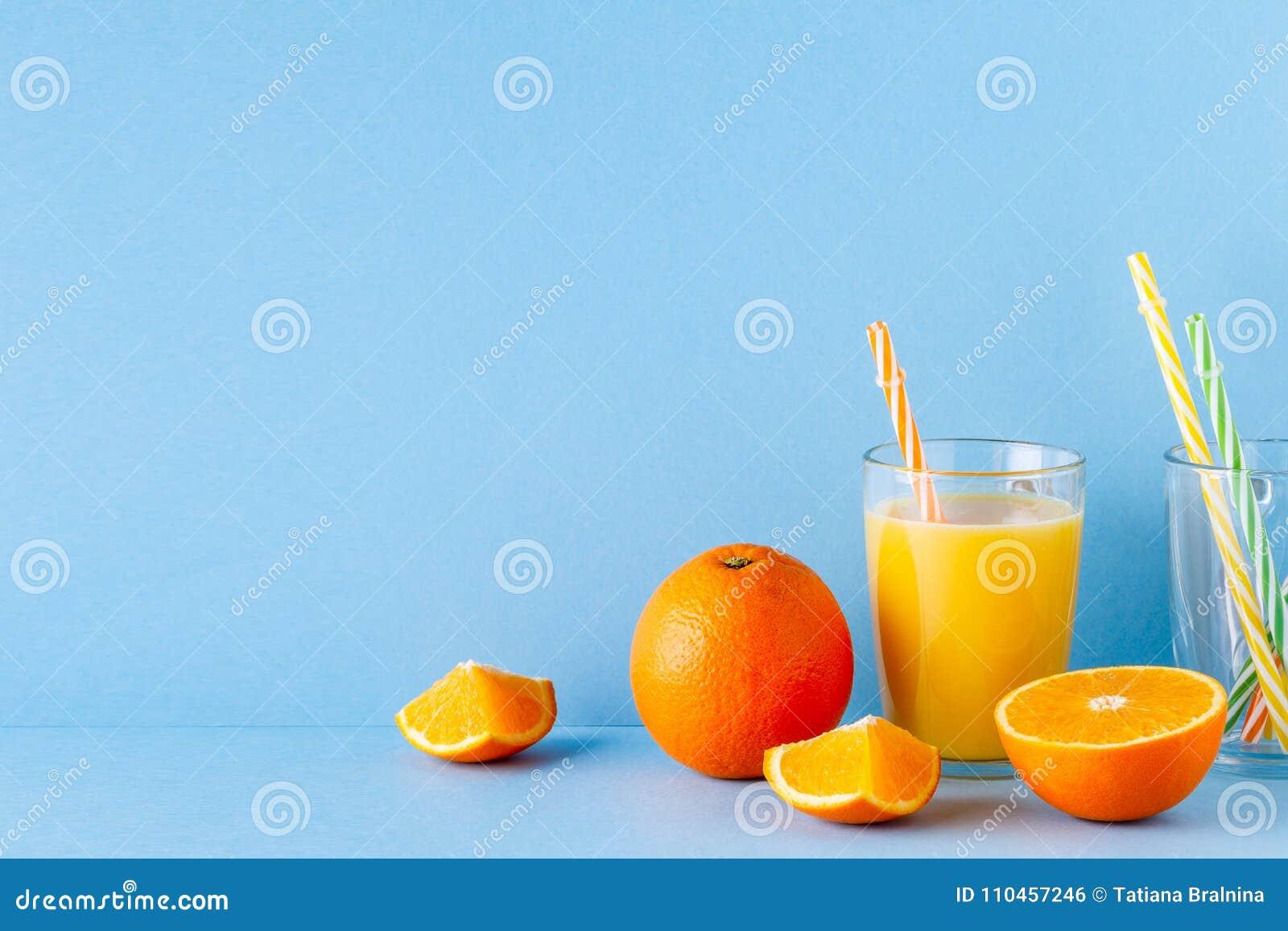 Orange fruktsaft på en blå pastellfärgad bakgrund