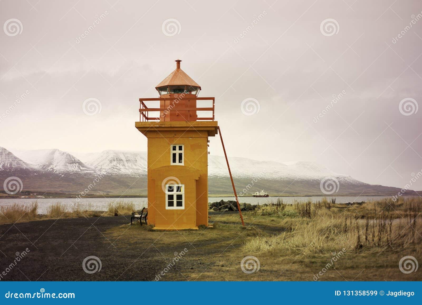 Orange Icelandic Lighthouse against mountain background
