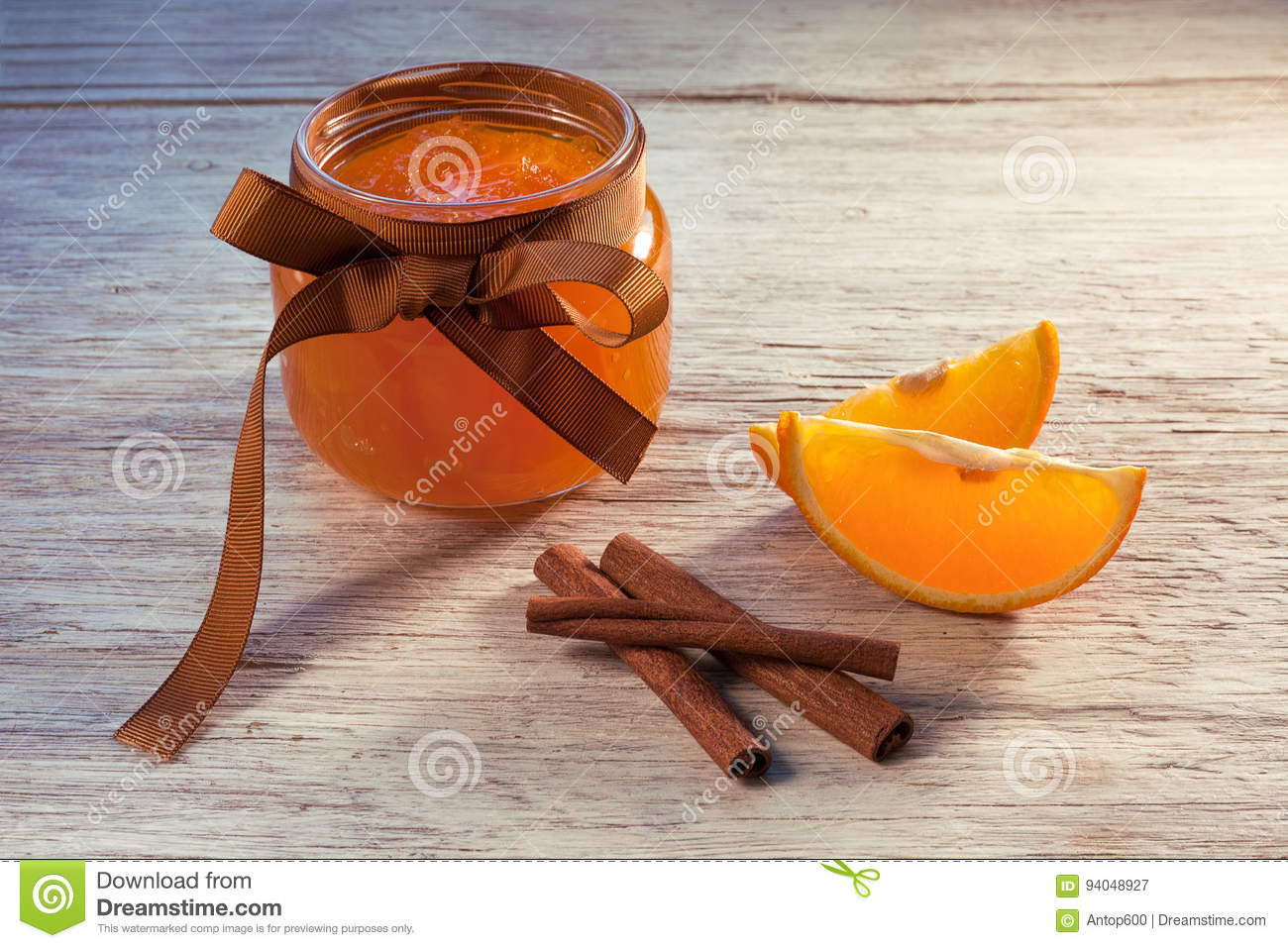 Orange jam in glass jar and pieces of orange on wooden table, fr