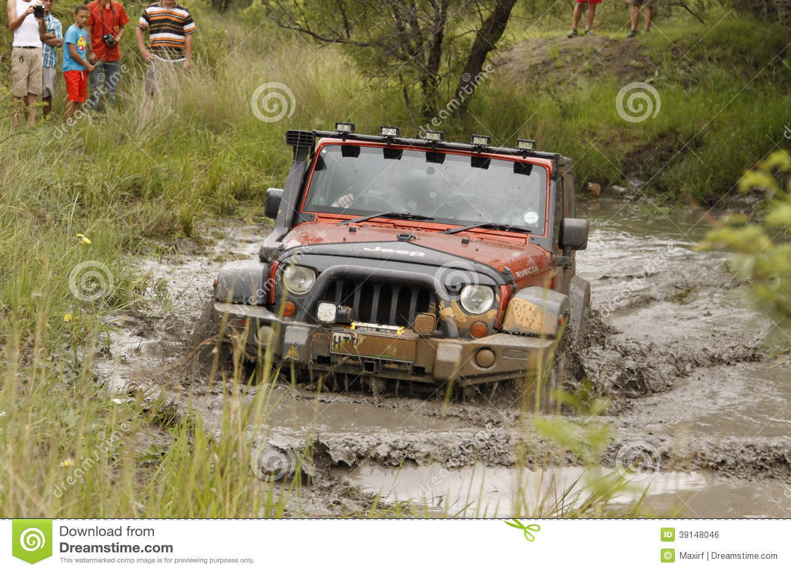 Orange Jeep Rubicon för fruktdryck korsning lerigt damm