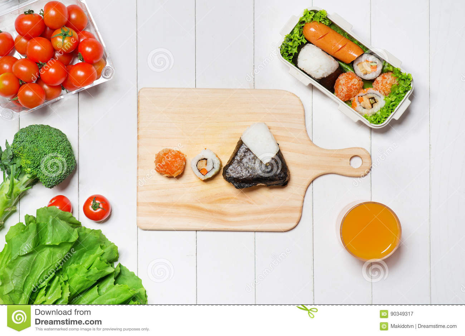 Orange juice and bento box with different food, fresh veggies an