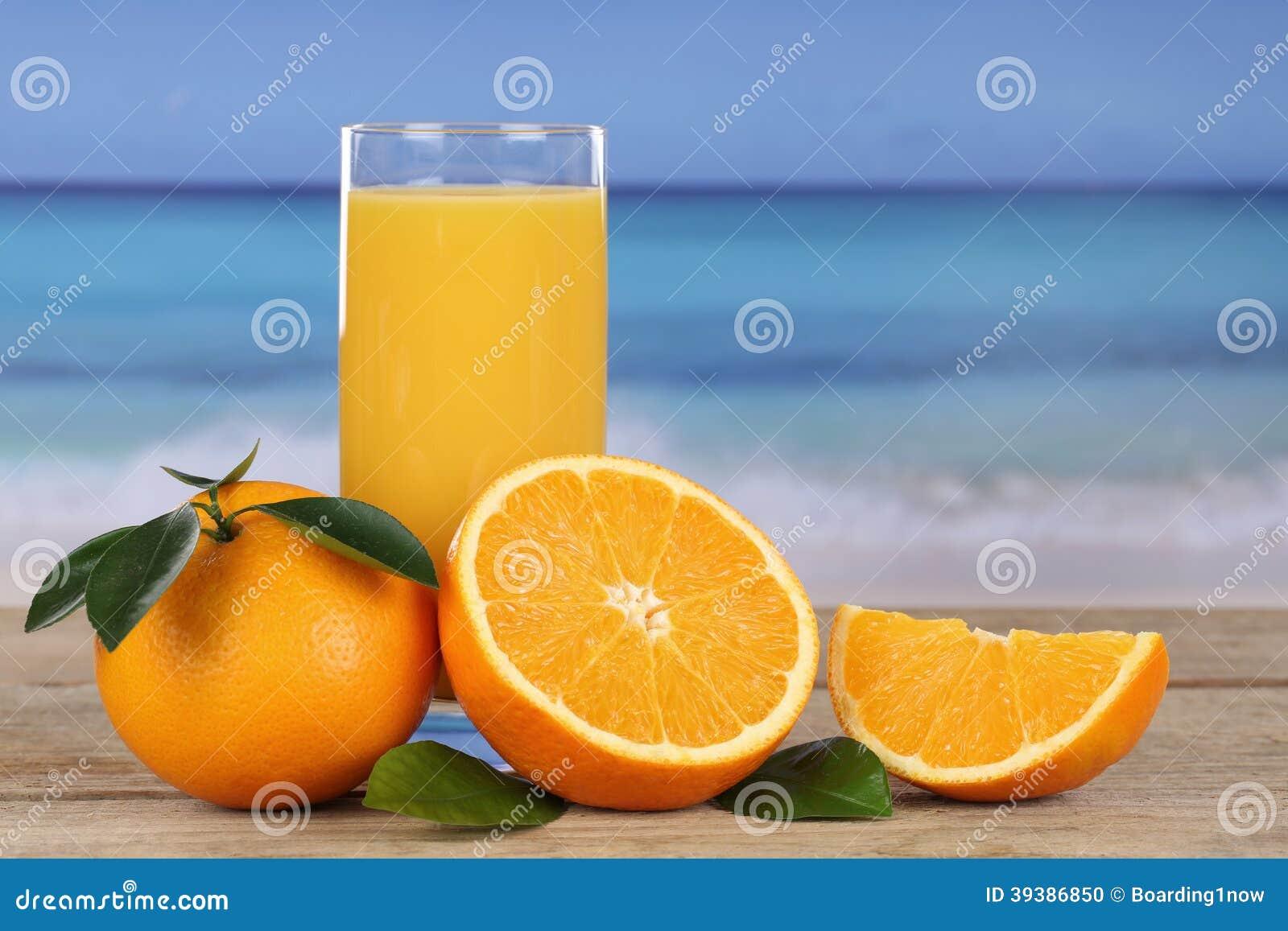 Orange juice and oranges on the beach