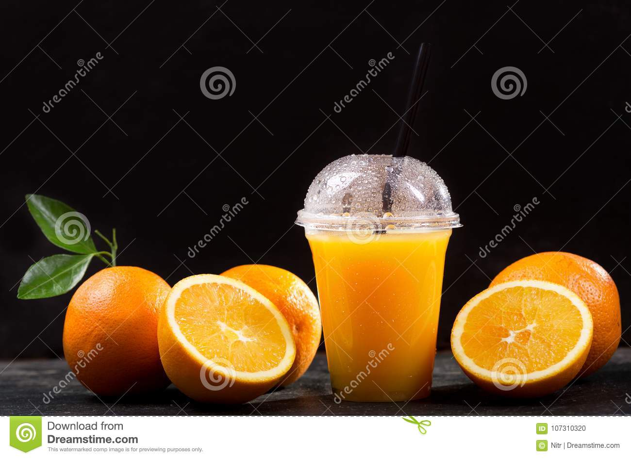 Orange juice in takeaway plastic cup with fresh fruits