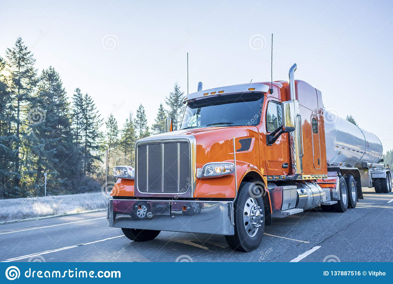 Orange klassisk amerikansk halv lastbil för stor rigg som transporterar vätskelast i den halva släpet för behållare som flyttar s