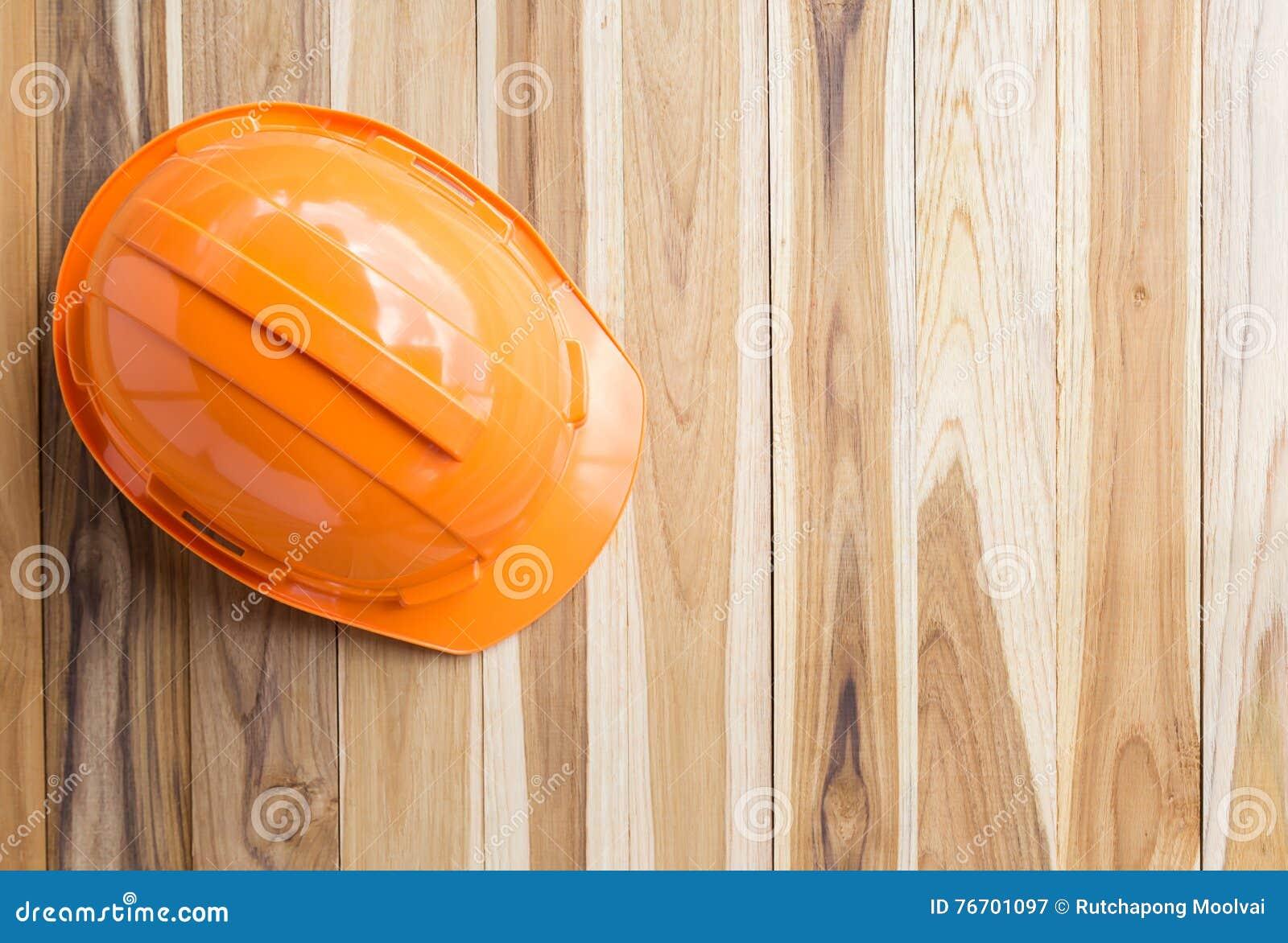 Orange kugghjul för hjälm för säkerhetstekniker på trätabellen