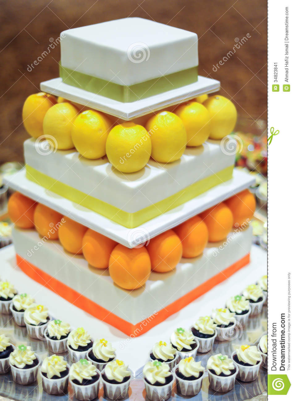 Orange Lemon 3 Tier White Wedding Cake With Mini Cupcakes Stock Image ...
