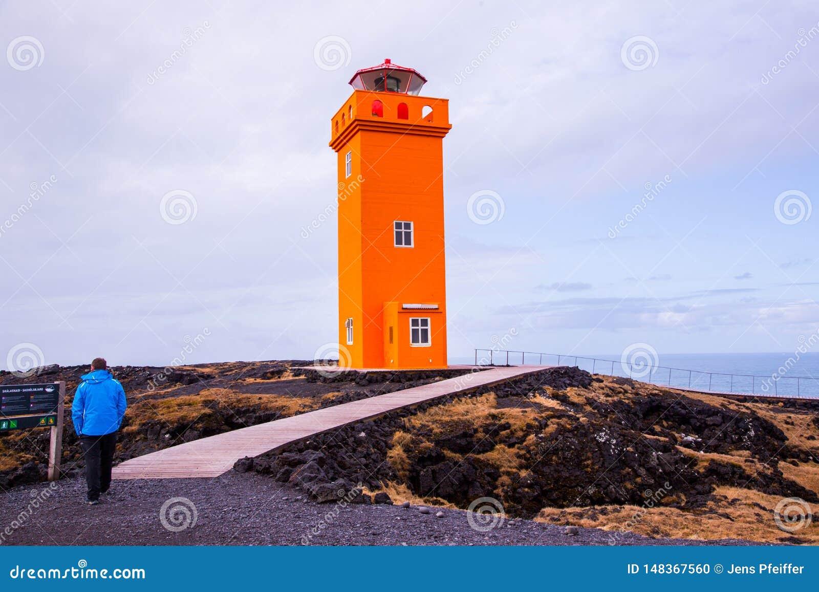Orange Leuchtturm mit Menschen im Vordergrund