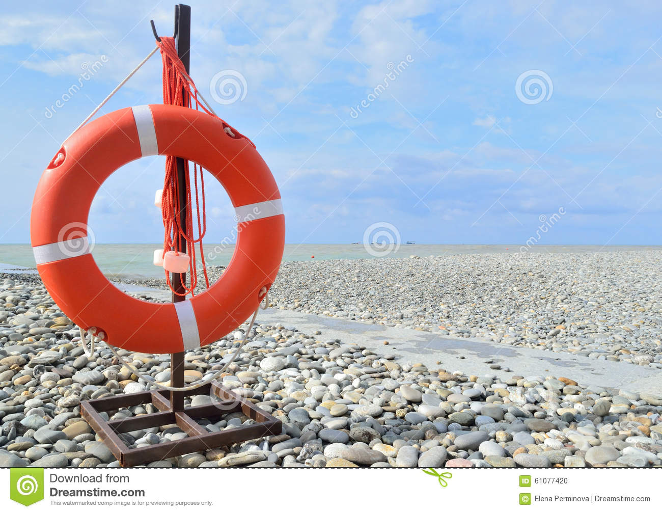 Orange lifebuoy attached to the seaside