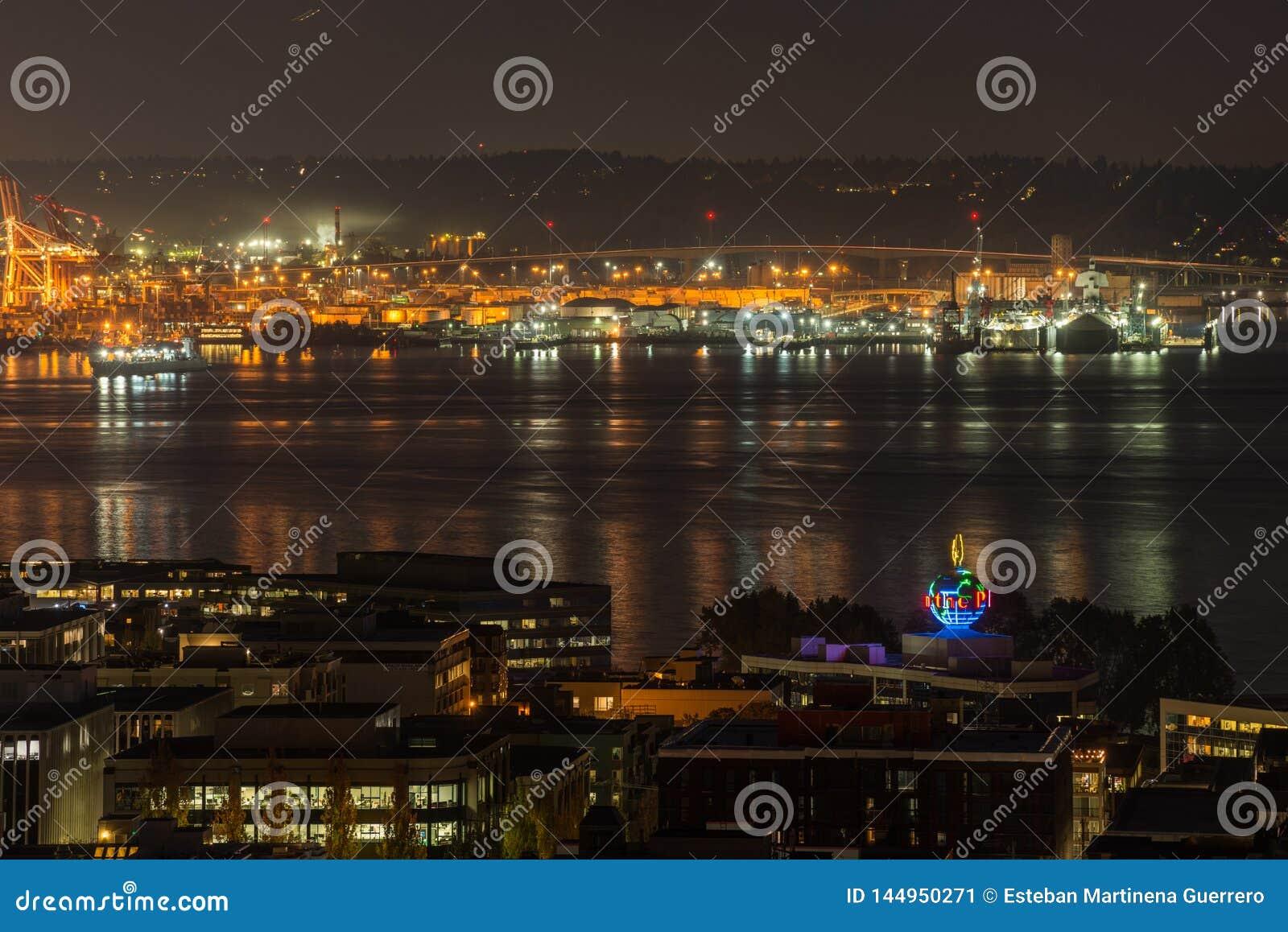 Orange lights iluminate the port of Seattle and Elliott Bay at night.