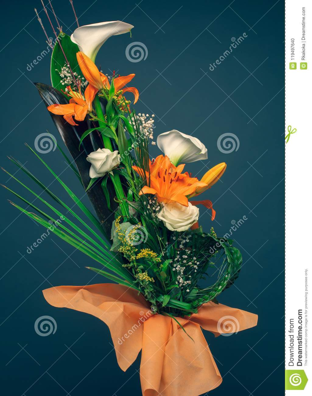 Orange lilies, white calla flowers and palm tree leaves bouquet vertical color image studio shot. Mothers day concept background,
