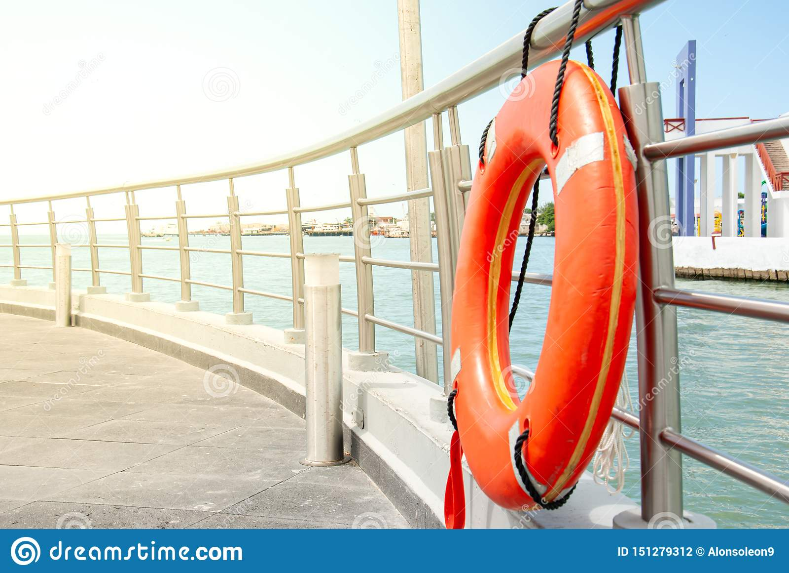 Orange livboj som förtöjas på räcket av skeppsdockan
