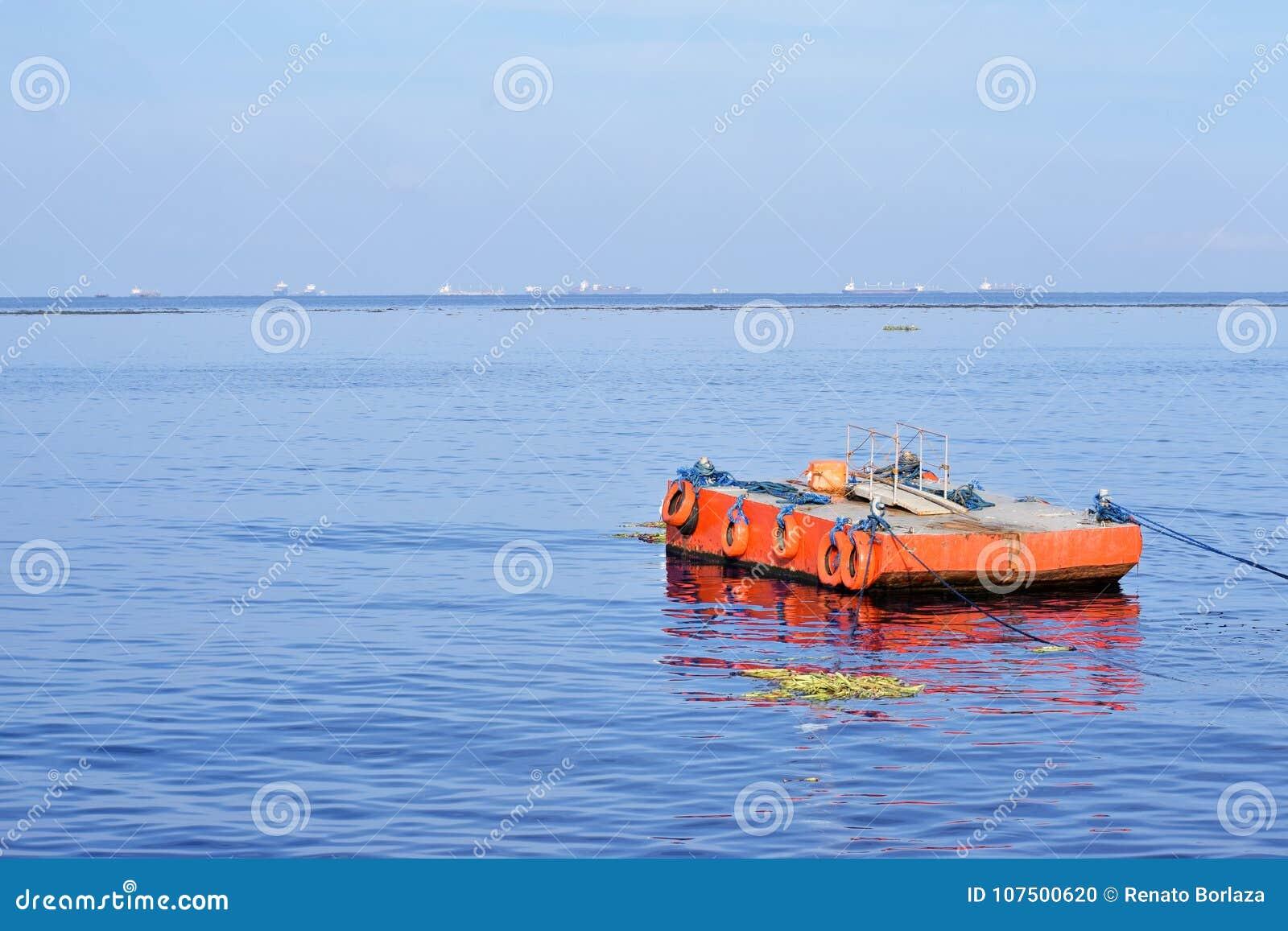 Orange malte Metalllastkahn verankert entlang Ozeanbucht