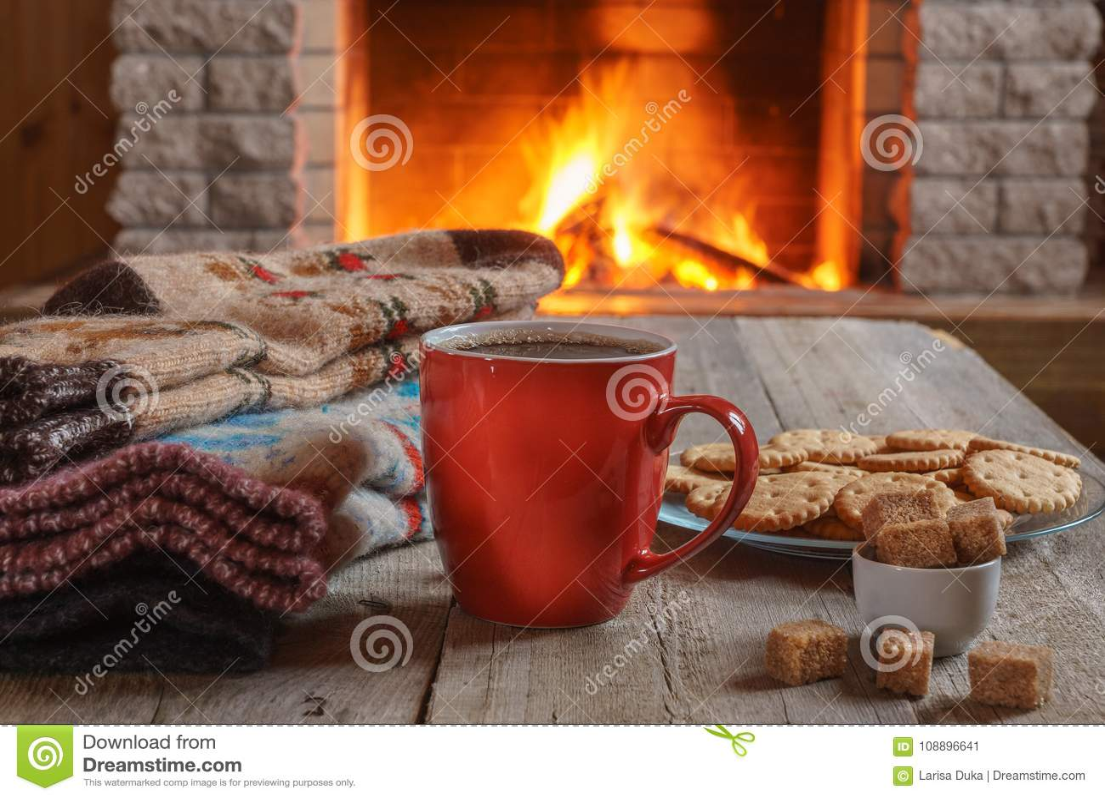 Orange mug for tea or coffee; wool things near cozy fireplace.