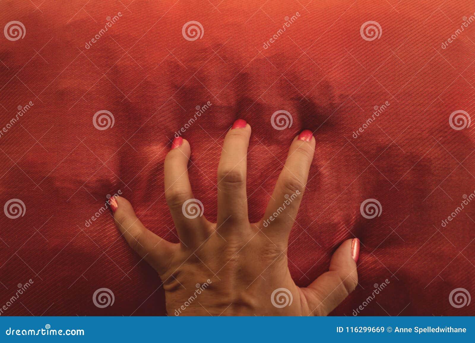 Orange Nagellack-Hand, die orange Kissen - zusammenpassende Farben ergreift