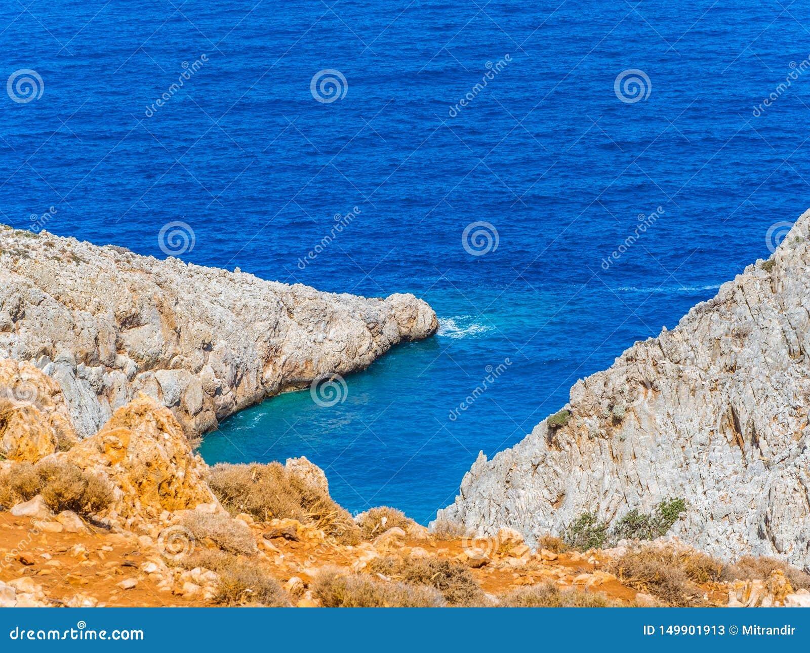 Orange och vita klippor och djupblått hav