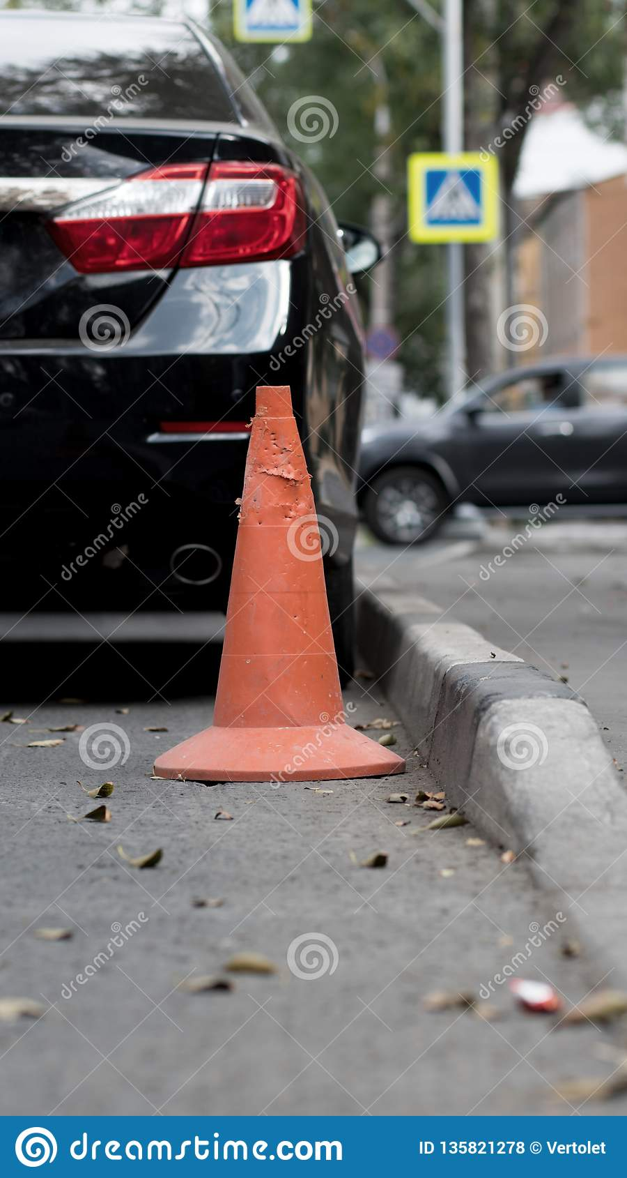 Orange old traffic cone on the road near a care