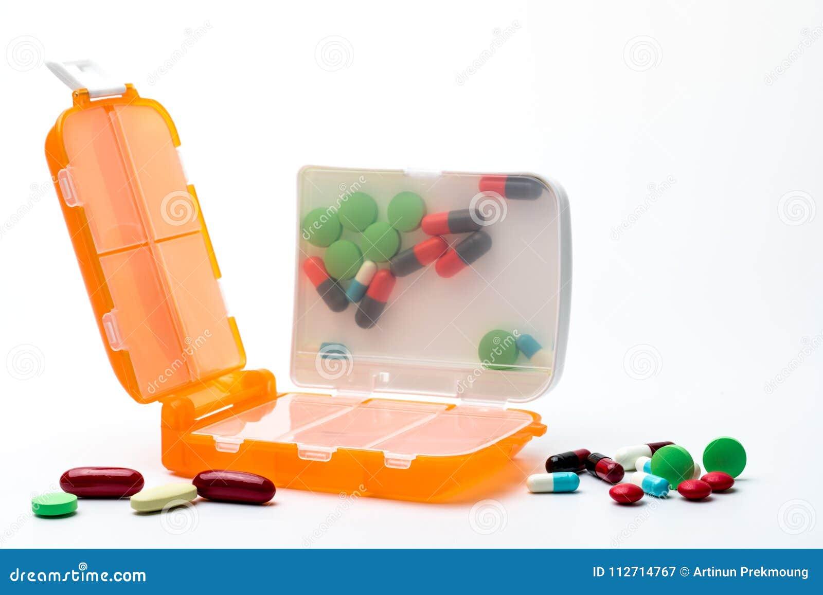 Orange Pillenkasten mit Tabletten und den Kapselpillen lokalisiert auf weißem Hintergrund mit Kopienraum