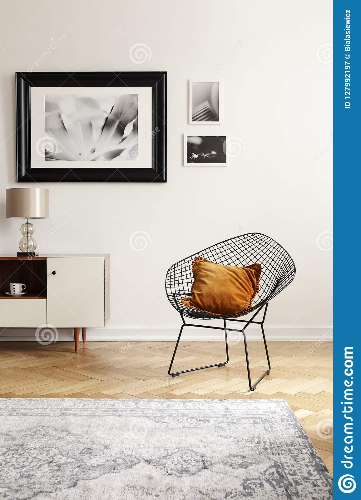 Orange pillow on a black, industrial net chair by a white wall with gallery of mock-up pictures in an elegant living room interior