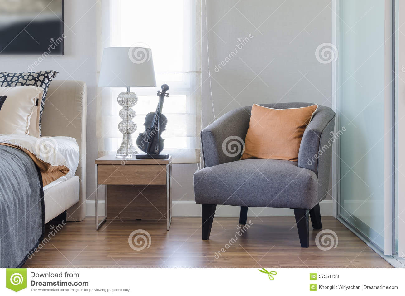 Orange Pillow On Modern Grey Chair With Bedside Table And