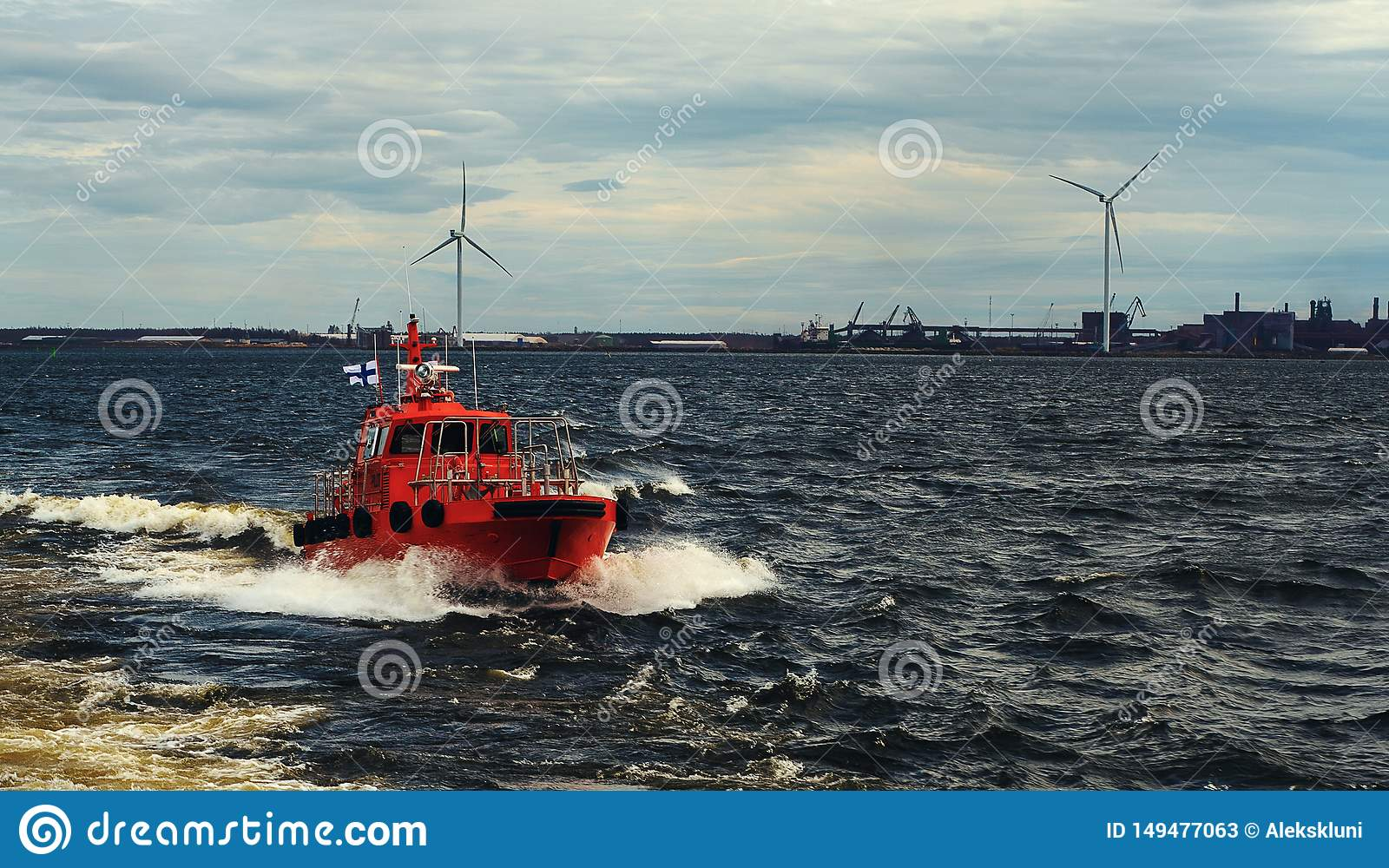 Orange pilot boat following for assistant to cargo vessel. Pilotage of vessel