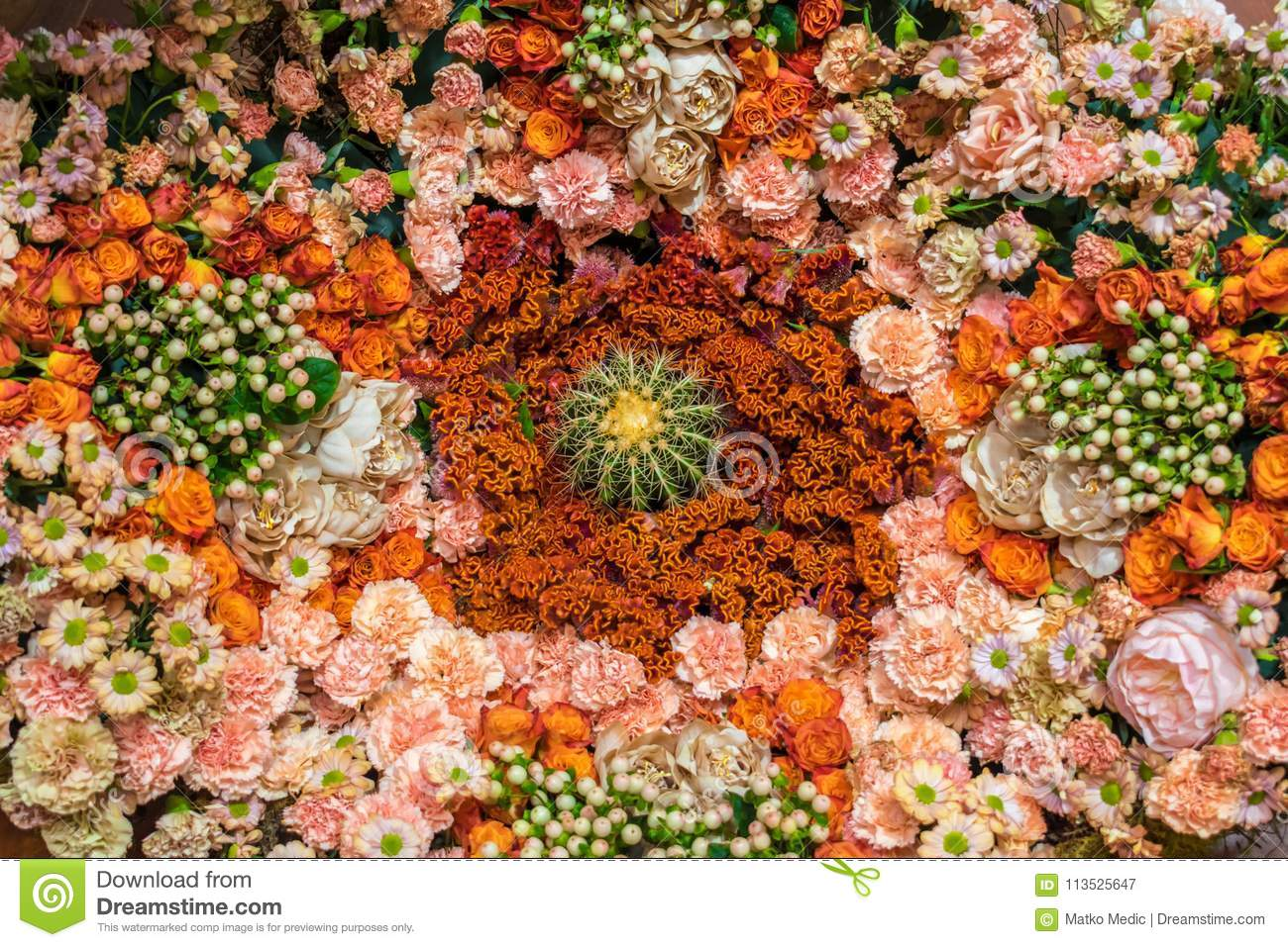 Orange and pink floral arrangement with cactus