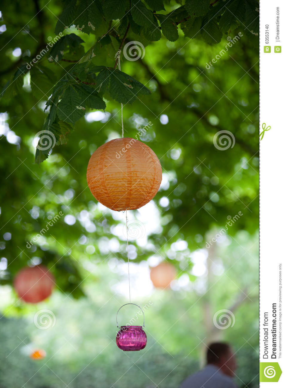 orange and pink lanterns and lights hanging from a green tree stock