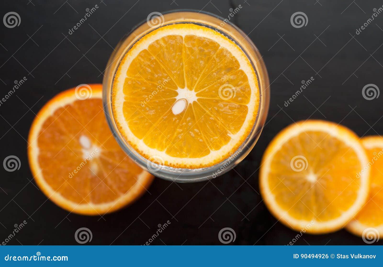 Orange Scheibe im Glas, die Ansicht von der Spitze, auf einem schwarzen hölzernen Hintergrund, Nahaufnahme,