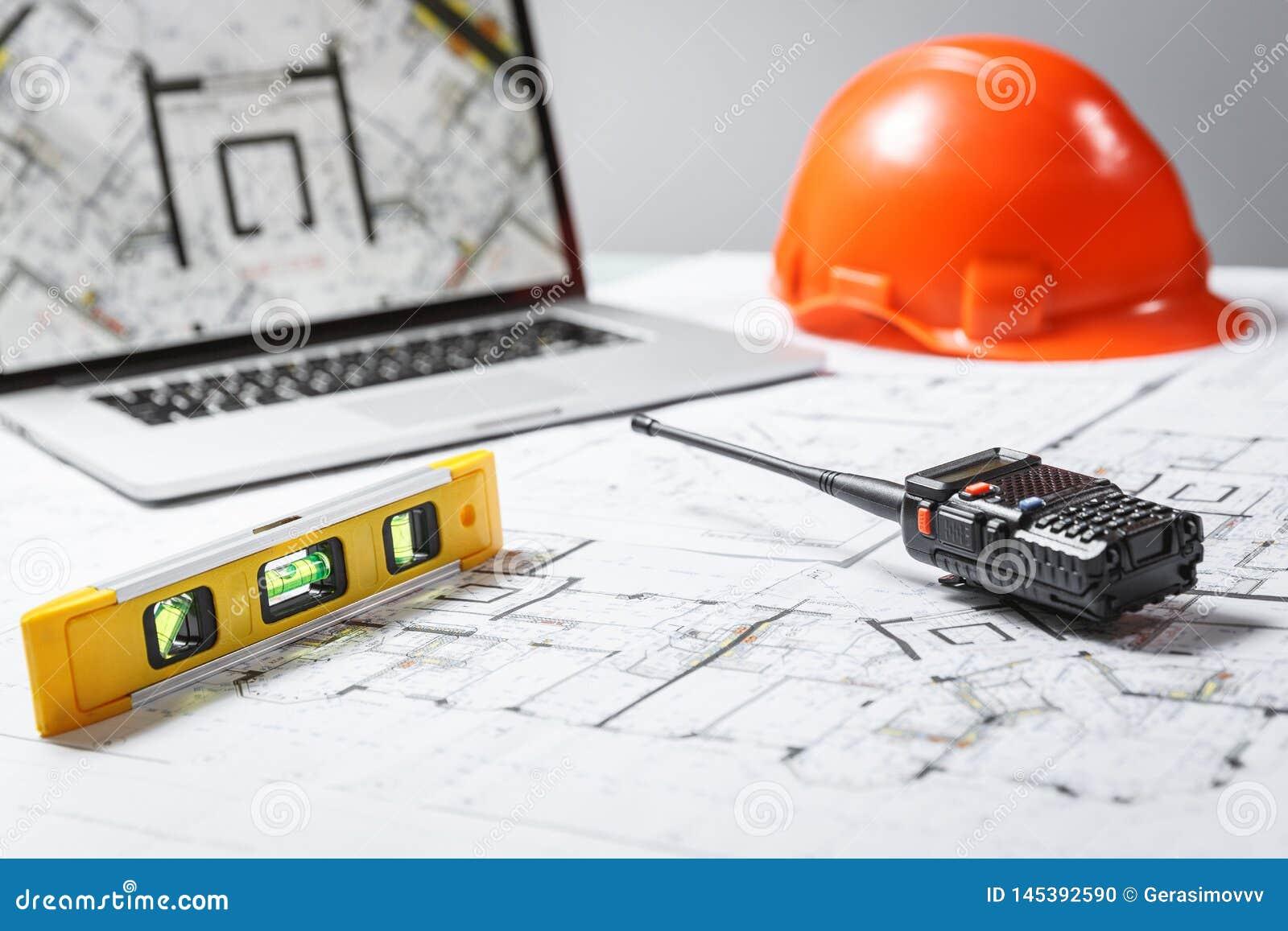 Orange Schutzhelm, Laptop mit Zeichnungen, waagerecht ausgerichtetes Meter und Funksprechgerät mit Plänen auf einer Tabelle