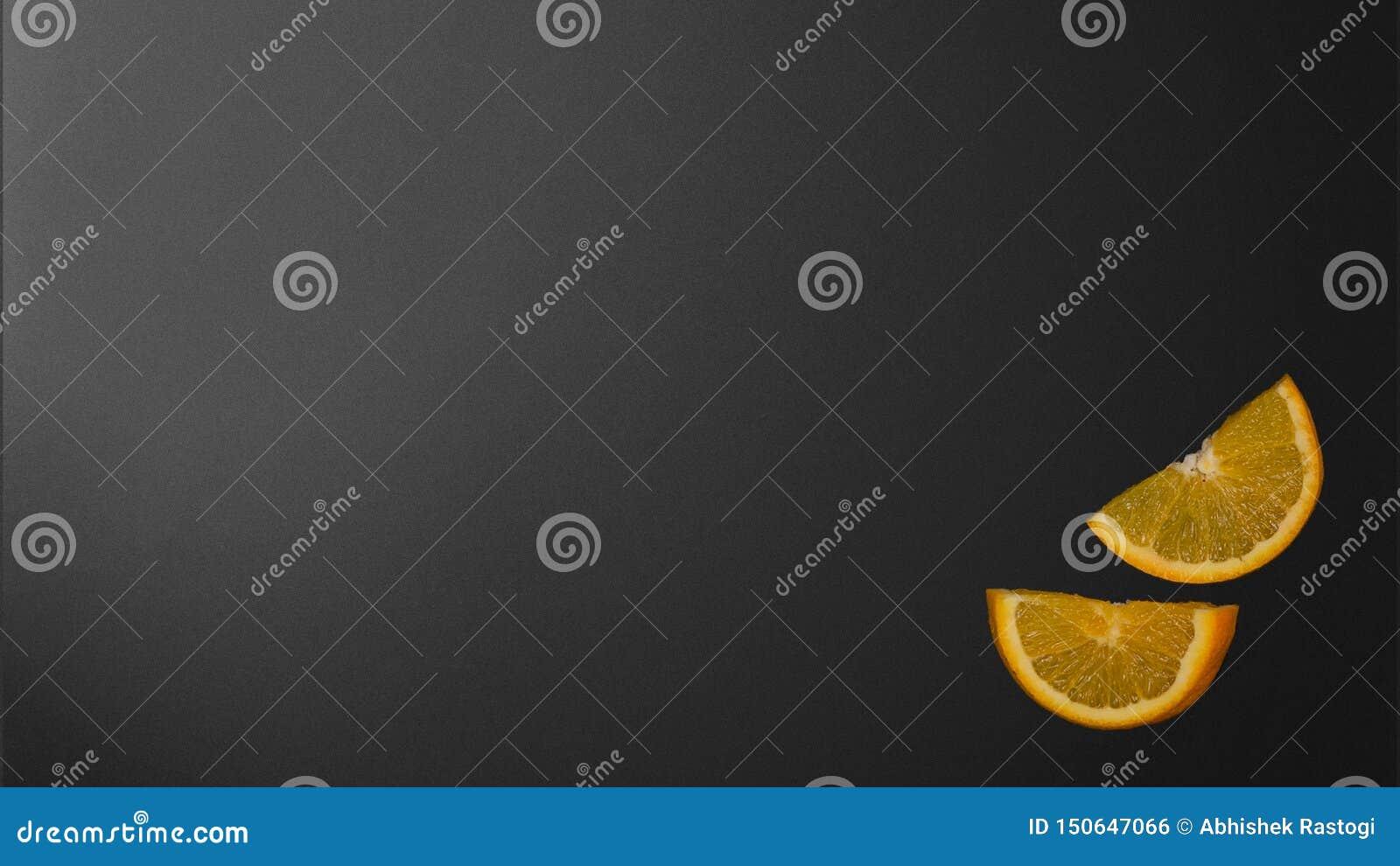 Orange skivor på den svarta bakgrunden i köket