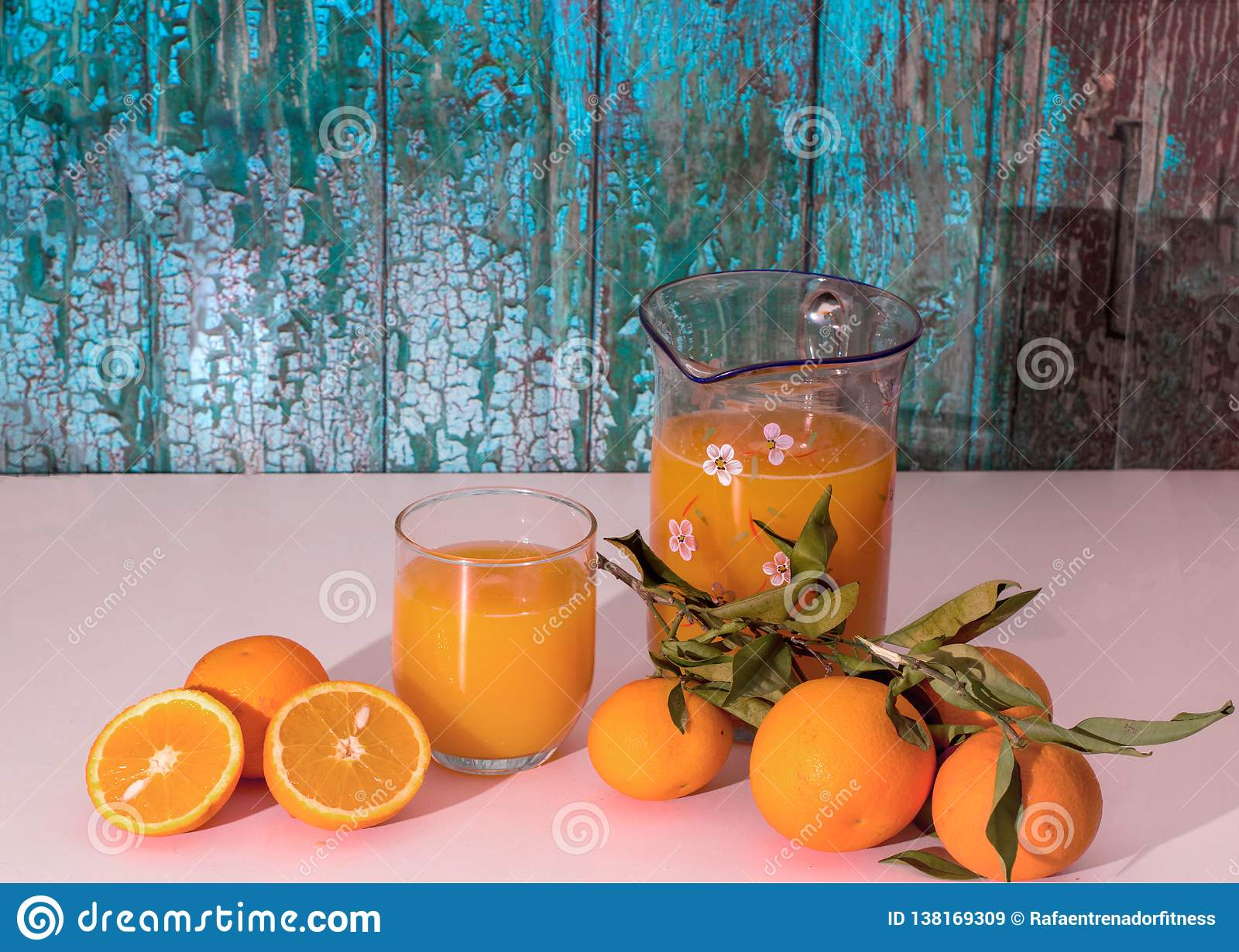 Orange split in half with a glass and a jug of orange juice