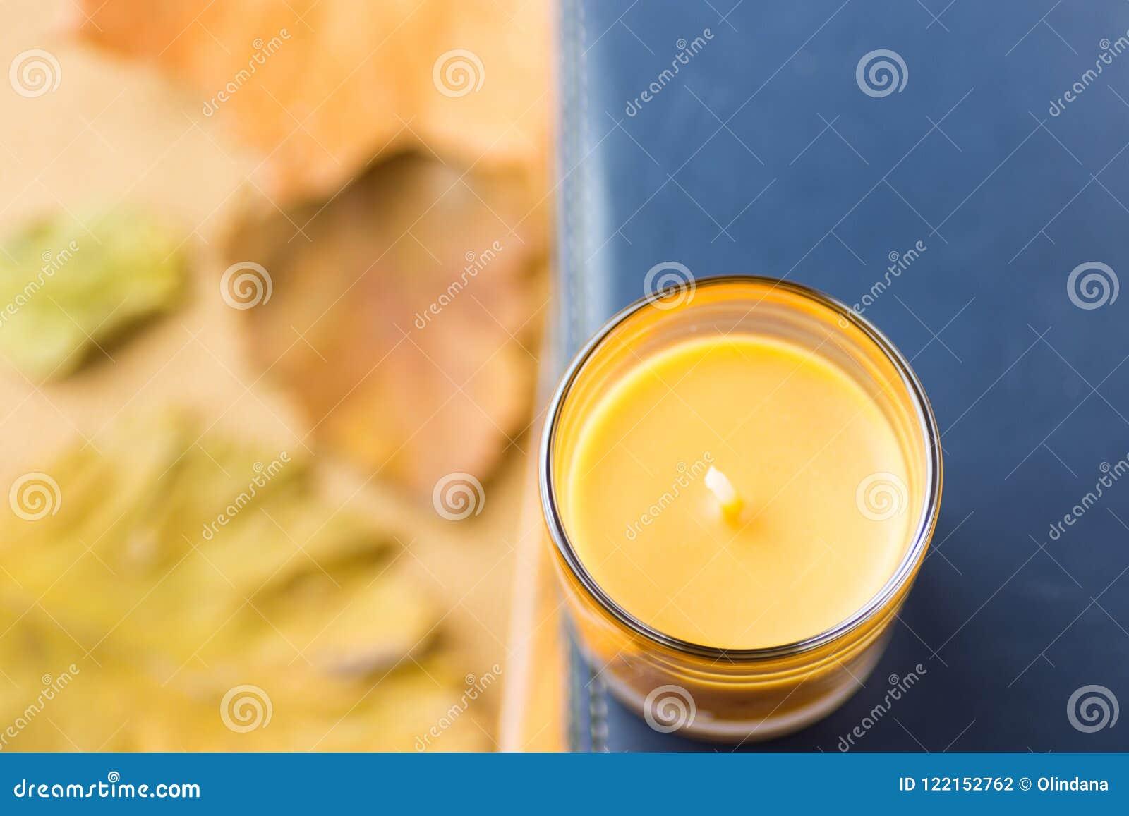 Orange stearinljus i den Glass hållaren på högen av bokmörker - blå marinbakgrund Torka gula röda Autumn Leaves Hemtrevlig nedgån