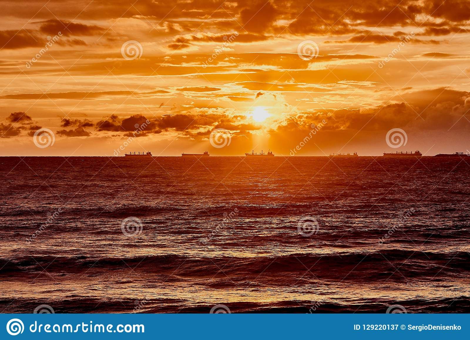 Orange sun with clouds over the gray sea with waves. The magical sunset on the Black Sea in Gelendzhik. Amazing natural background