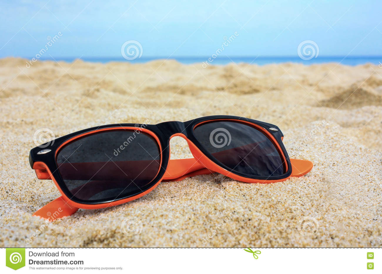 62e0c3f0f8e8 Orange-black sun-glasses on the golden sand with the sea blue water and sky  on the background. Location Costa Rei, Sardinia, Italy.